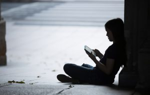 Teen girl sits against wall in shadow, saddened by her iPAd