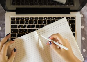 Female student writes in a notebook while using her laptop