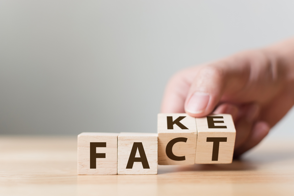 "Wooden blocks spell out ""fact"" but a hand turns them to spell ""fake"""