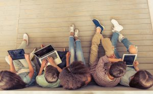 View from above of five teenagers using iPads and laptops while sitting on a wooden floor