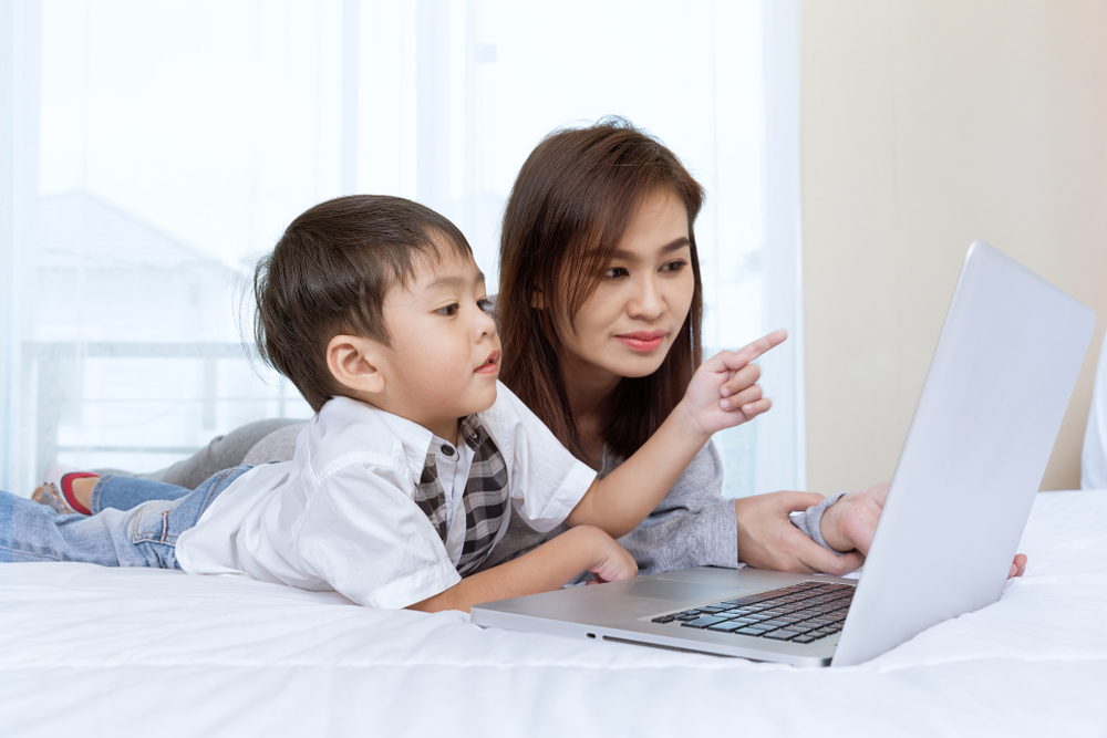 Mother and son look at laptop together.