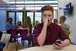 Nervous boy in cafeteria, phone in hand.