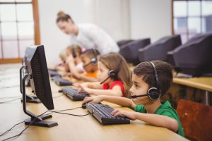 Elementary school students use headsets in computer class.