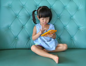 Child uses tablet while sitting on couch.