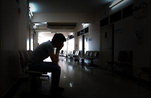Depressed teen sits in dark hallway.