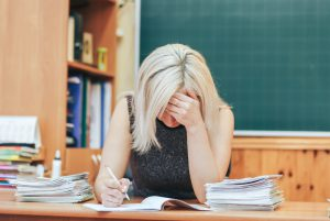 Stressed teacher grading a pile of papers