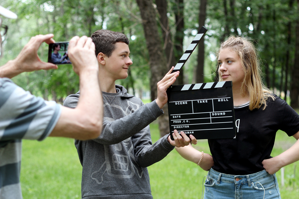 Teens film a scene with smartphone