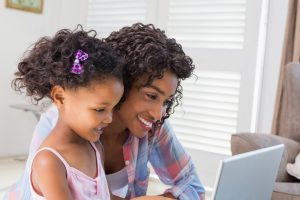 Mother shows her daughter how to use a laptop.
