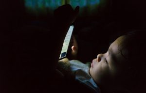 Young boy with tablet in bed