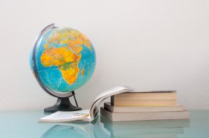 Globe, notebook and stack of textbooks