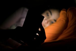 girl in bed on phone