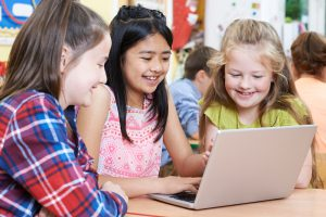 three students looking at laptop