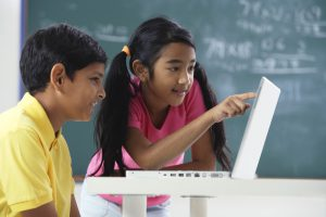 Two young students work at laptop.