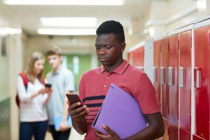 Young male holding a binder and looking at his cell phone upset while two other students are laughing in the background in front of some lockers.