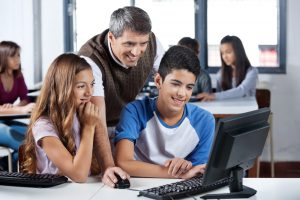Administrator helps happy students with computer.