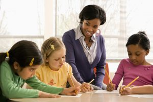 Teacher works on writing with three students