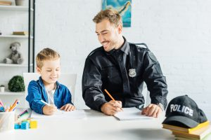 Smiling school resource officer counsels child.