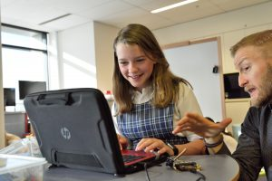 Teacher helps computer student.