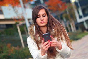Sad teens surfs internet on phone.