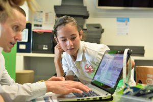 Girl watches teacher use laptop.