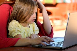 Little girl sits in mother's lap and looks at computer.