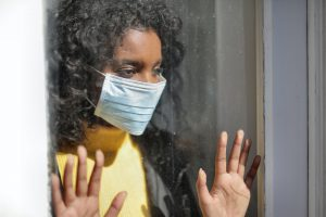 Young girl wearing mask looks out window.