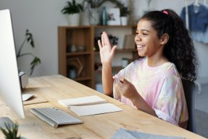 Young girl raises hand at computer while distance learning.
