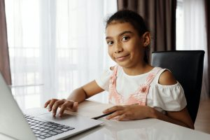 Young girl using laptop looks at camera and smiles.