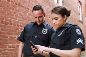 Two school resource officers look at an alert on a cell phone