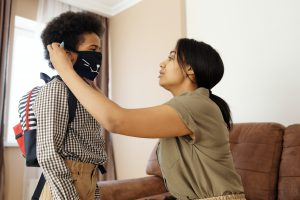 Mother putting a mask on her son's face before school.