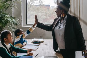 Teacher high-fives smiling student.